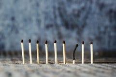 Спички стоят в ряд на серой предпосылке, одном burne спички Стоковые Фотографии RF
