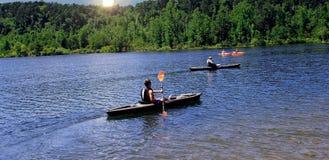 Сплавляться на красивом озере с Солнцем над деревьями стоковое изображение