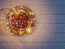 Сплетенное красное сердце внутри больших стеклянных изделий на светлой деревянной предпосылке Стоковое фото RF