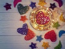 Сплетенное красное сердце внутри больших стеклянных изделий на светлой деревянной предпосылке Стоковая Фотография
