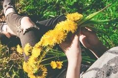 Сплетите венок желтых одуванчиков в руках девушек Стоковое Изображение RF