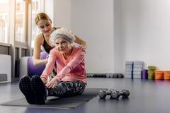 Спокойная бабушка делая разминку в спортзале стоковое фото