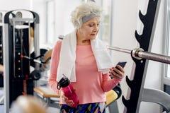 Спокойная бабушка наблюдая на мобильном телефоне стоковые фотографии rf