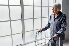 Спокойная бабушка наблюдая на окне в больнице стоковые фотографии rf