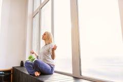 Спокойная девушка делая раздумье около окна стоковое изображение rf