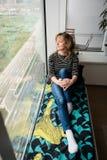 Спокойная женщина сидя около окна Стоковое Изображение