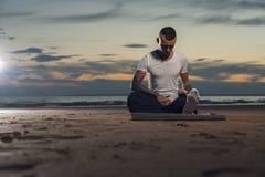 Спокойная йога молодого человека практикуя на пляже Стоковое фото RF
