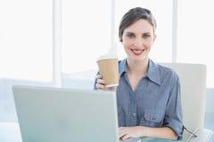 Спокойная красивая коммерсантка показывая устранимую чашку пока сидящ на ее столе Стоковая Фотография RF