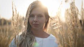 Спокойная молодая белокурая женщина смотря камеру стоя в поле сток-видео