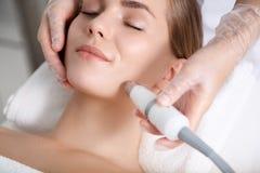 Спокойная молодая женщина получая обработку кожи подмолаживания кавитации Стоковое Фото