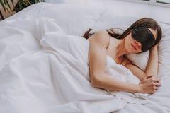 Спокойная молодая женщина спать в светлой кровати стоковое изображение rf