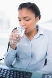Спокойная молодая темная с волосами питьевая вода коммерсантки Стоковые Изображения