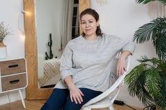 Спокойная привлекательная женщина сидя в стуле ротанга в отечественной комнате за зеркалом, смотря камеру стоковые изображения rf