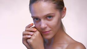 Спокойная привлекательная кавказская девушка смотря ровный на камере и касаясь ее чисто коже нежно, был нагой в светлой студии видеоматериал