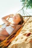 Спокойная усмехаясь молодая женщина лежа в гамаке в ярком свете солнца стоковая фотография
