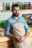 Спокойное дружелюбное предприниматель удобного кафа стоя и усмехаясь добросердечно стоковое изображение rf