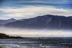 Спокойное изображение горы, океана, света, и облаков нижнего яруса стоковое изображение rf