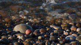 Спокойное море океанских волн с чистой водой ласкает камни и звук конца-вверх камешков воды сток-видео