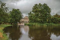 Спокойное озеро с лужайкой, рощей здание и облачное небо в парке Амстердама стоковое изображение