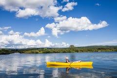 Спокойное река и женщина ослабляя в каяке Стоковое Изображение