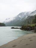 Спокойное река с песчаным пляжем на предпосылке Стоковые Фотографии RF