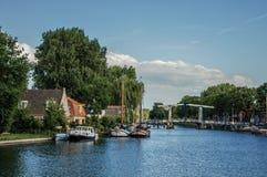 Спокойное река с рощей и мостом, шлюпками причалило в пристани домов кирпича и солнечном голубом небе в Weesp Стоковое Изображение RF