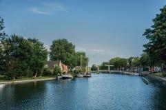 Спокойное река с рощей и мостом, шлюпками причалило в пристани домов кирпича и солнечном голубом небе в Weesp Стоковые Изображения RF