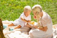Спокойные дети есть помадки в парке стоковая фотография