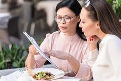 Спокойные женщины выбирая блюдо на таблице Стоковое фото RF