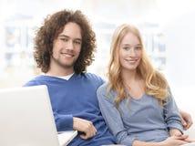 Спокойные молодые усмехаясь пары с компьтер-книжкой Стоковые Изображения RF