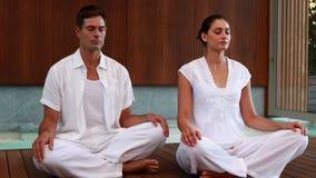 Спокойные пары в белом усаживании в лотосе представляют сток-видео
