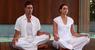 Спокойные пары в белом усаживании в лотосе представляют видеоматериал