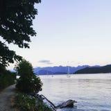 Спокойный вечер в Howe Sound, вне Gibsons, ДО РОЖДЕСТВА ХРИСТОВА, Канада Парусник плавает через стекловидный океан на пути к Gibs стоковое изображение