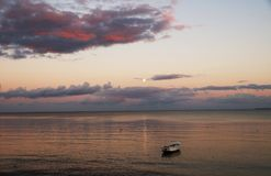 Спокойный вечер на океане с драматическими облаками на заходе солнца стоковая фотография