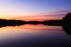 Спокойный взгляд спокойного озера и захода солнца заволакивает Стоковое Фото