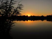 Спокойный заход солнца на озере с тросточкой Стоковые Фото