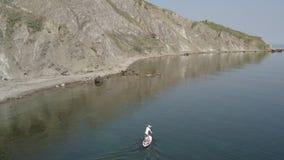 Спокойный seascape с горами в предпосылке Вдоль человека маленького глотка побережья плавая сток-видео