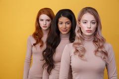3 спокойных женщины стоя в студии стоковая фотография