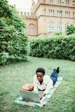 Спокойствие, который нужно работать outdoors Молодой афро американский студент лежа на траве принимая примечания на кампусе на ко стоковое фото