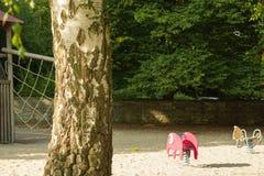 Спортивная площадка детей на деятельностях при двора публично паркует окруженный зелеными деревьями на утре солнечного света стоковое изображение