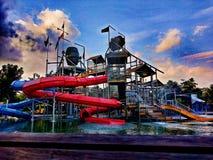 Спортивная площадка парка водных горок делает детьми счастье стоковые изображения