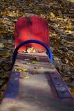 Спортивная площадка с красной шалью для 2 детей Старая слезая краска, солнечная золотая осень стоковая фотография