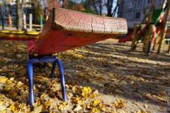 Спортивная площадка с красной шалью для 2 детей Старая слезая краска, солнечная золотая осень стоковые изображения rf