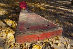 Спортивная площадка с красной шалью для 2 детей Старая слезая краска, солнечная золотая осень стоковое фото
