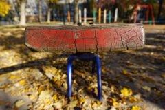 Спортивная площадка с красной шалью для 2 детей Старая слезая краска, солнечная золотая осень стоковое фото rf