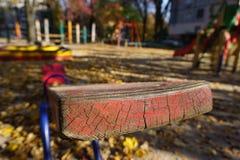 Спортивная площадка с красной шалью для 2 детей Старая слезая краска, солнечная золотая осень стоковые изображения