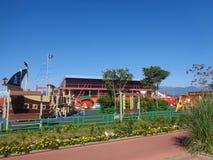 Спортивная площадка ` s детей, лужайка с цветками и зеленые деревья вокруг Стоковые Изображения RF