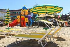 Спортивная площадка, шезлонги и зонтики детей на пляже стоковое изображение