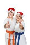 2 спортсмена в крышке Санта Клаусе показывают палец супер Стоковые Изображения