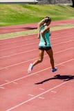 Спортсменка бежать на гоночном треке Стоковые Изображения